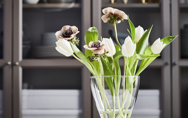 A small bouquet of white tulips, brownish poppies and fresh green leaves in a curvy VASEN vase in front of a cupboard.