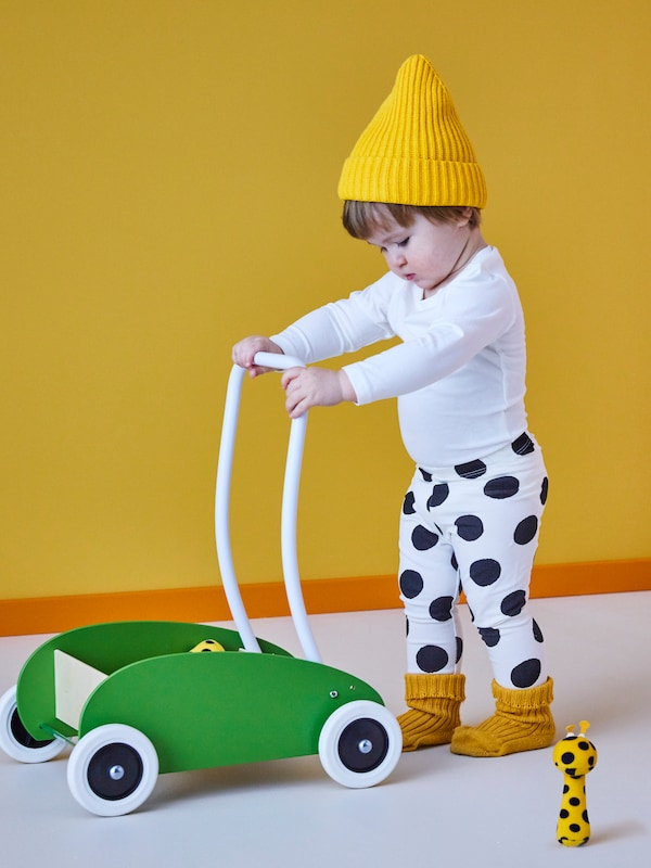 A small boy in a yellow woolly hat pushing MULA green child's trolley with a KLAPPA small soft toy and a yellow wall.