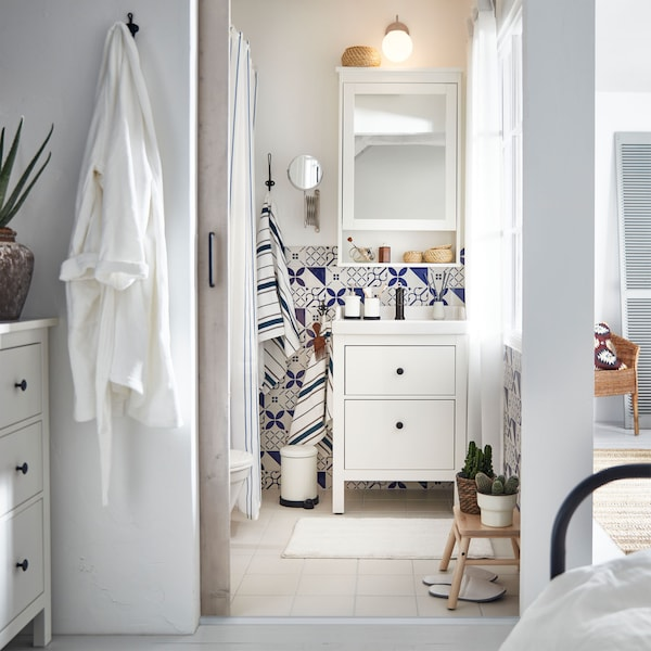 A small, bright and airy bathroom with blue patterned tiles, an IKEA HEMNES/RÄTTVIKEN wash-stand and mirrored wall cabinet.