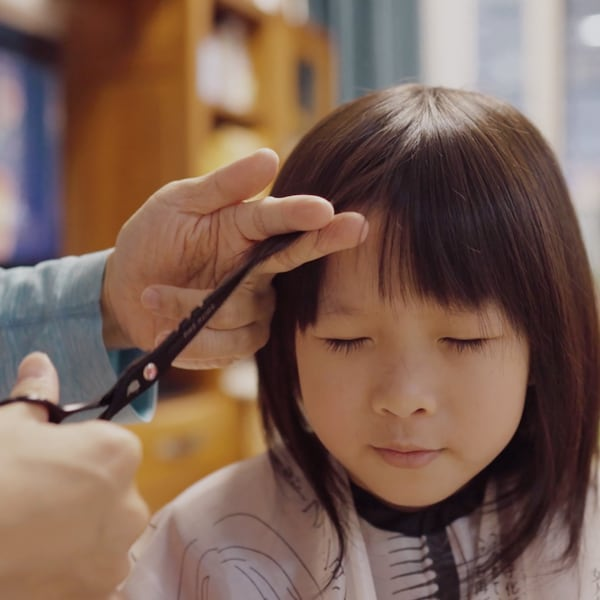 A small child closes her eyes while her bangs are being trimmed with scissors.