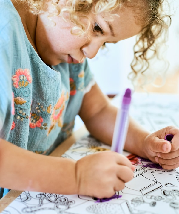 A small child colouring in an illustration with a purple crayon.