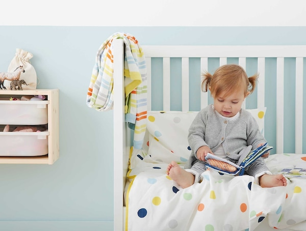 A small child reading a book in bed.