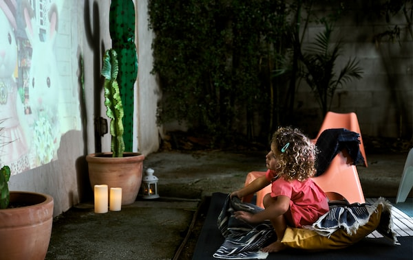 A small child sitting on blankets and cushions watching a cartoon projected on an exterior wall, next to a potted cactus and LED candles.