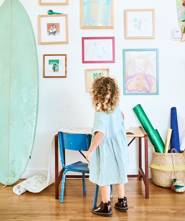 A small child stands in front of a small desk and chair, looking up at a wall of their paintings and family photographs next to a surfboard.