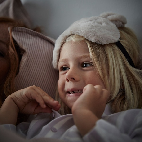A small child with long blonde hair lies back on a soft pillow while wearing a fluffy eye-mask on the top of their head.
