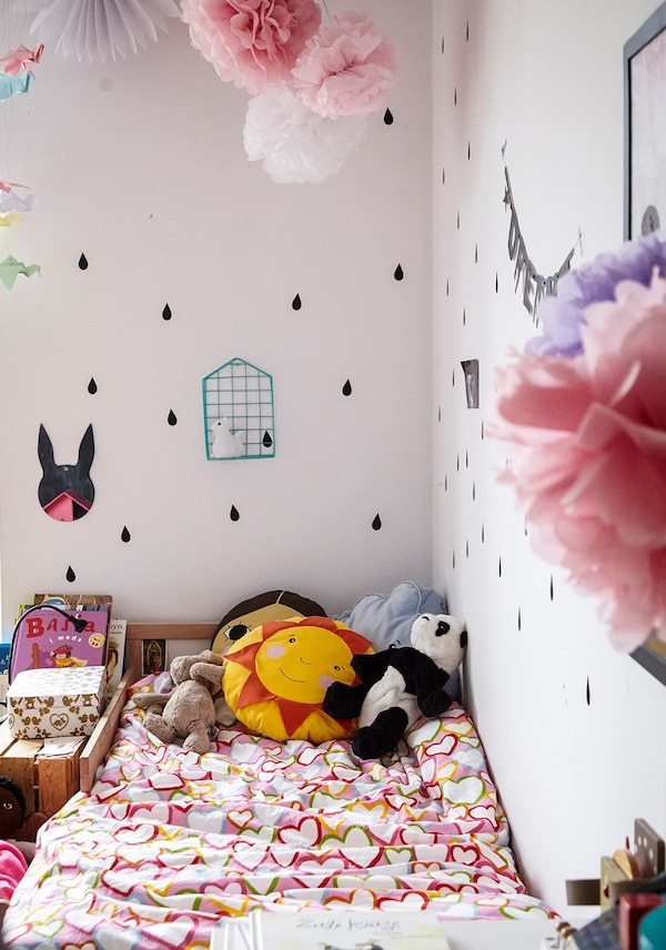 A small children's bed, with bedlinen covered in hearts and soft toys.