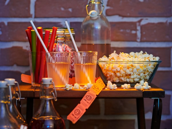 A small folded table is set up with movie snacks. A clear glass bowl of popcorn, two clear glass drinks with white straws and a container of snacks are on the table and the setting is dark, as if the sun is setting.