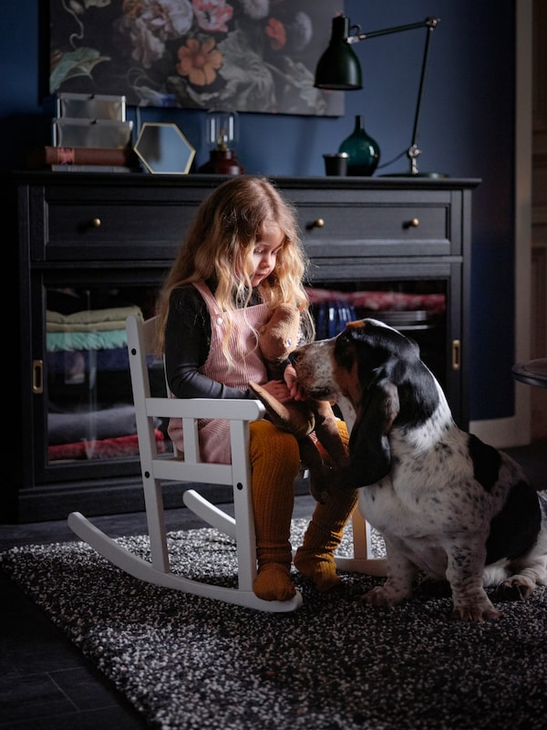 A small girl sits on a SUNDVIK rocking chair in a dark living room, while a basset hound rests its head in her lap.