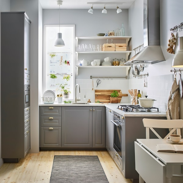 A small grey and white kitchen with BODBYN grey kitchen drawer fronts and brass-colour ENERYDA knobs and cup handles.