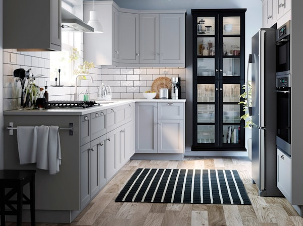 A small grey and white traditional styled kitchen with LERHYTTAN grey kitchen cabinet doors and black stained glass doors.