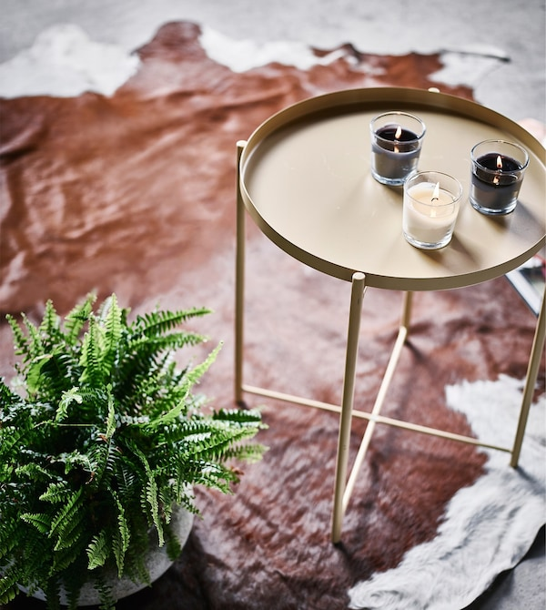 A small indoor fern next to a side table sitting on a cowhide rug.