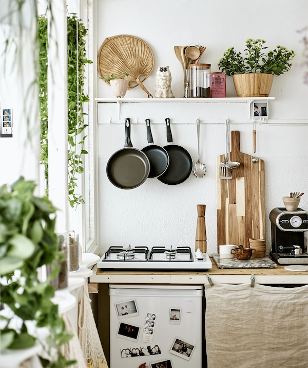 A small kitchen with hob, hanging utensils and a shelf for display.