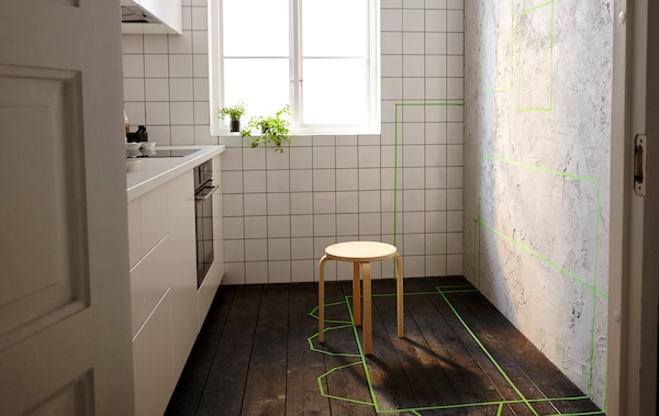 A small kitchen with one unfinished wall. Green tape marks the future placement of storage furniture, tables and chairs