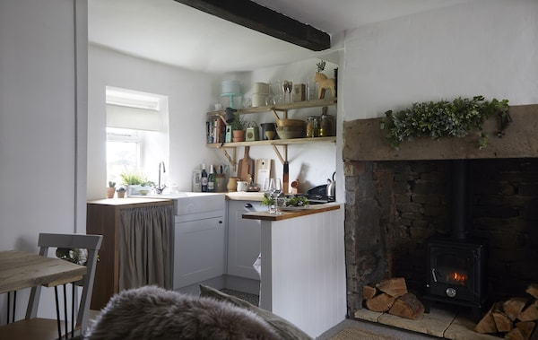A small kitchen with open shelves above the worktop, next to a large fireplace.