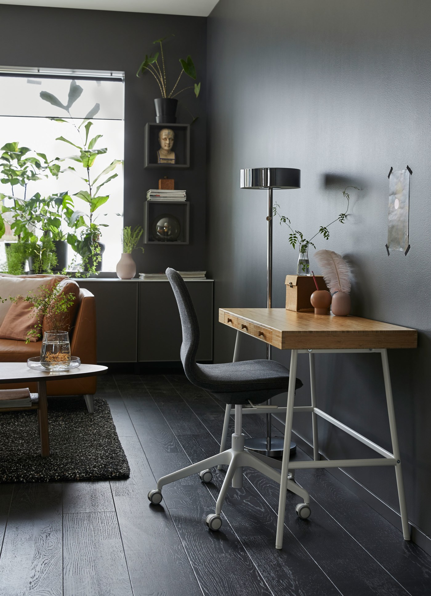 A small LILLÅSEN work desk with a bamboo worktop surface and white legs against a dark grey sitting room wall.
