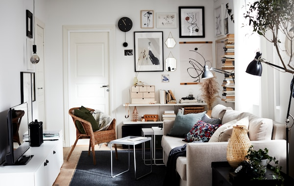 A small living room area with lots of light, a sofa, a TV, a vertical book display and an art wall, all in neutral colours.