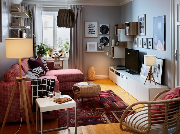A small living room with a red Persian patterned rug, a red sofa, grey curtains, an armchair in rattan and mood lighting.
