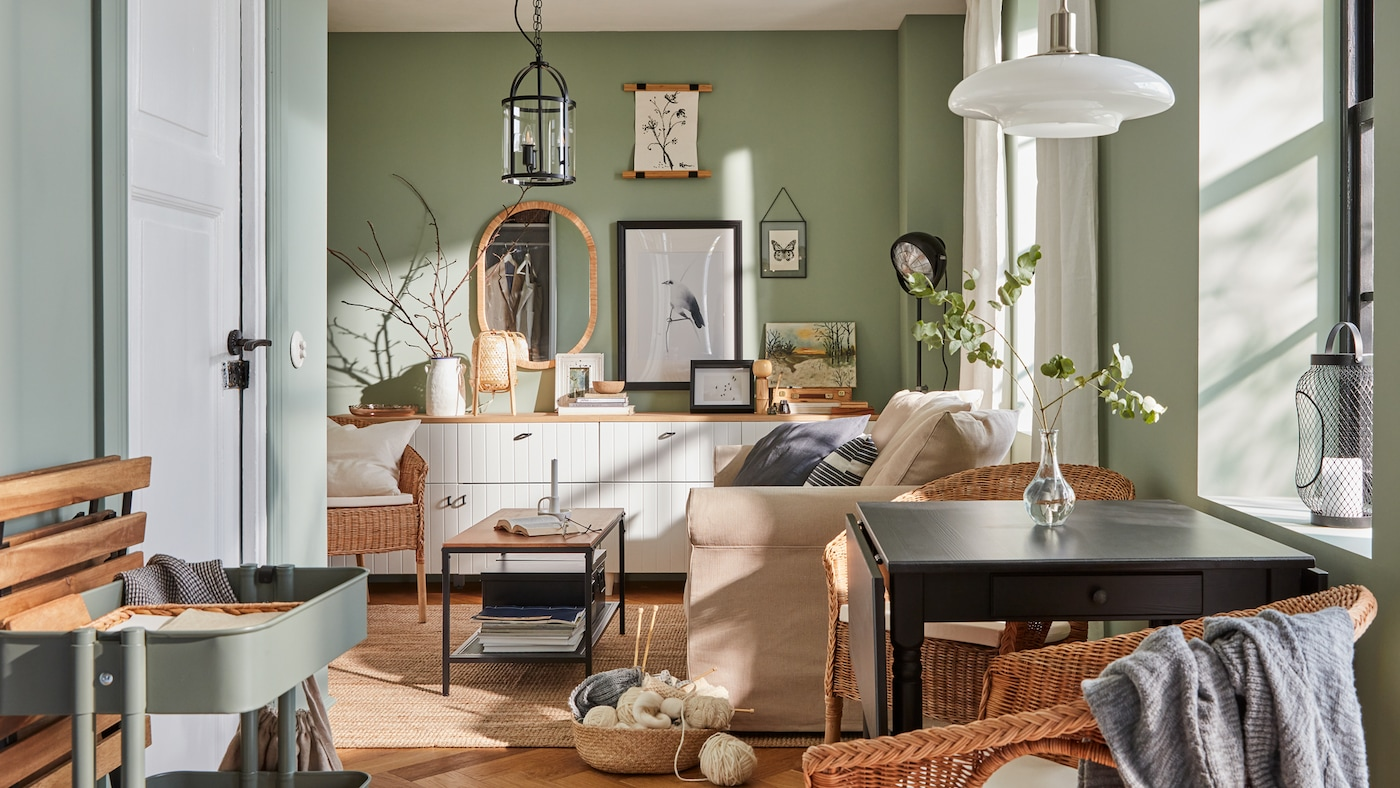 A small living room with green walls, a sofa, a small dining nook and framed posters and pictures on the wall.
