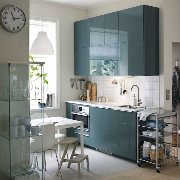 A small, modern kitchen with white walls and splash-back and high-gloss grey-turquoise KALLARP doors.