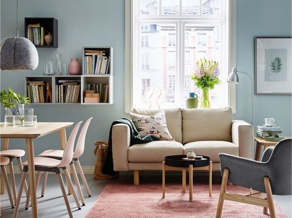 A small open-plan living room / dining area with the NORSBORG 2-seat sofa in Edum beige and VEDBO armchair in grey.