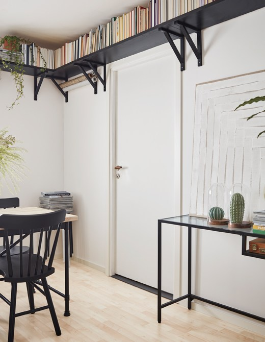 A small room with a dining table, glass desk and black book shelves mounted high along the ceiling to make it feel airy.