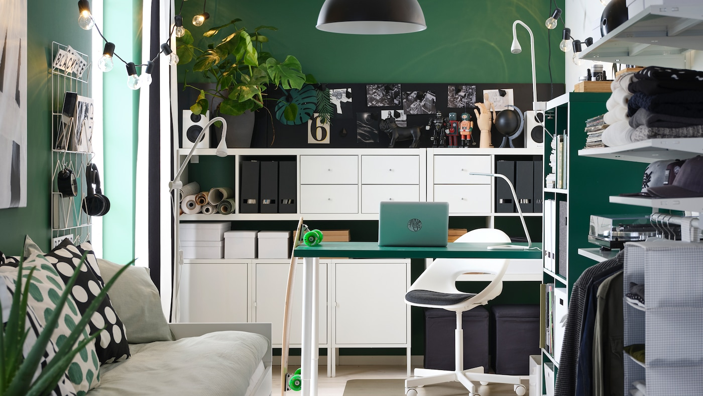 A small room with a green desk, white shelving units, a day-bed, an open wardrobe and a black pendant lamp.