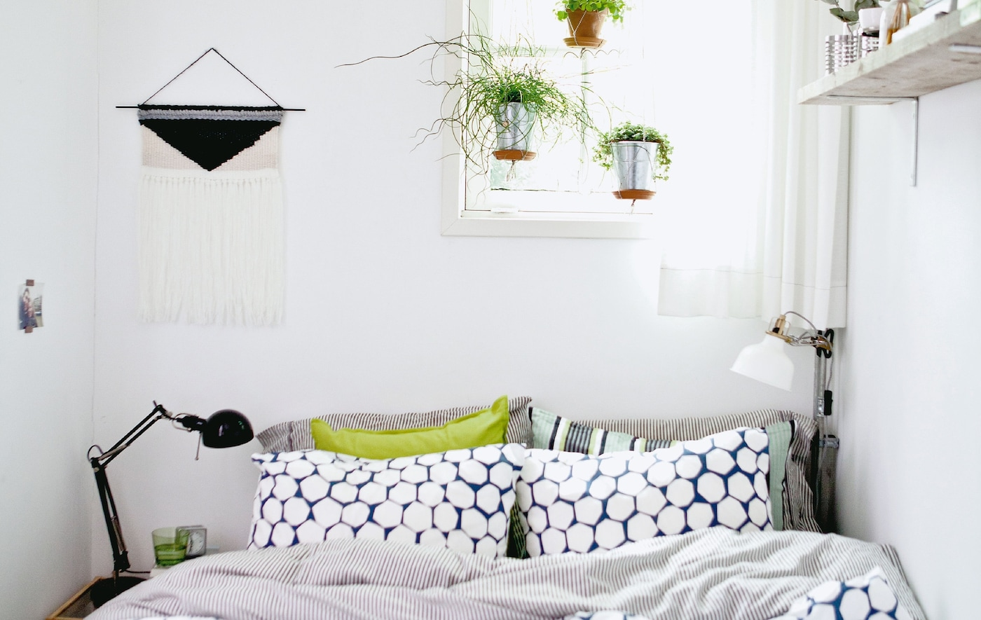A small room with double bed, hanging plants and shelf.