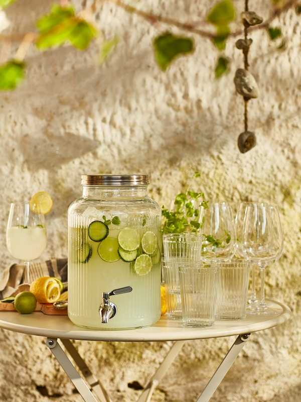 a small round table set outside with a glasses and VARDAGEN jar with tap full full of limeade.