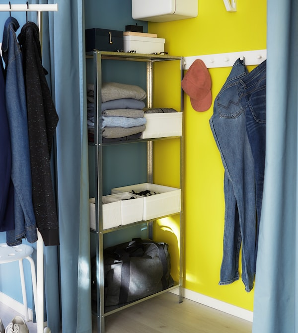 A small shelving unit and hooks help to keep a closet functional and organised.