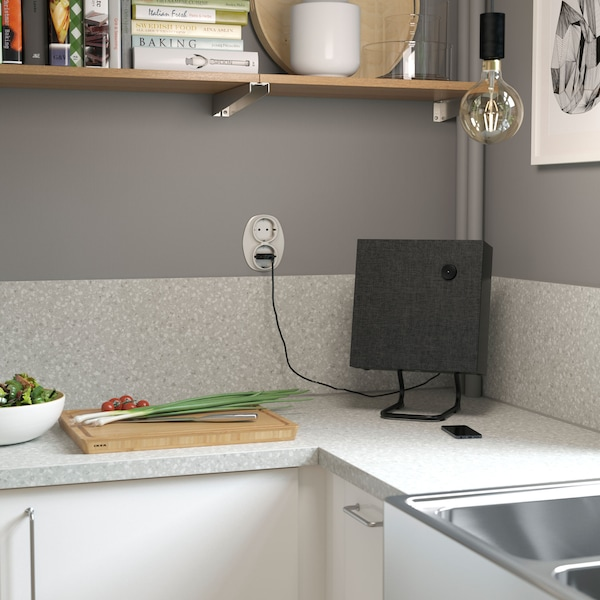 A small, square shaped IKEA ENEBY black Bluetooth® stereo speaker, in a kitchen corner on the worktop.