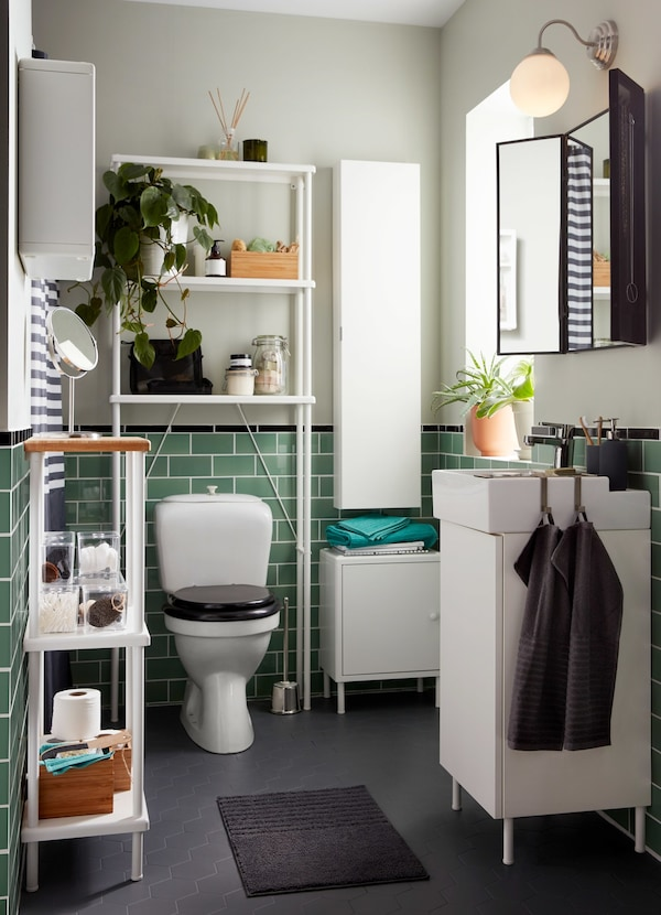 A small white bathroom with green tiles and a grey floor and a white LILLÅNGEN wall cabinet and washbasin cabinet.