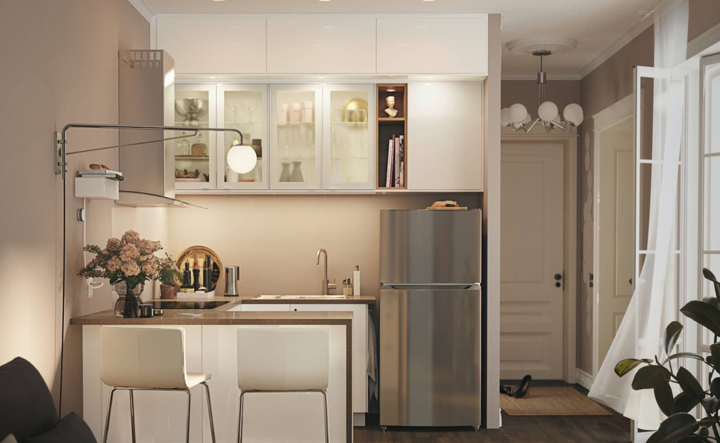 A small white kitchen consisting of a refrigerator and base cabinets, drawers, a worktop and a wall cabinet.