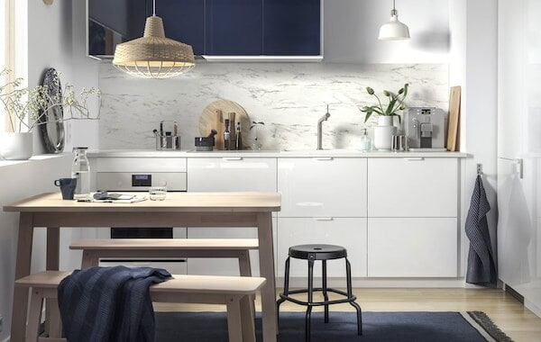 A small, white kitchen with marble effect splashback and dark blue wall cabinets.