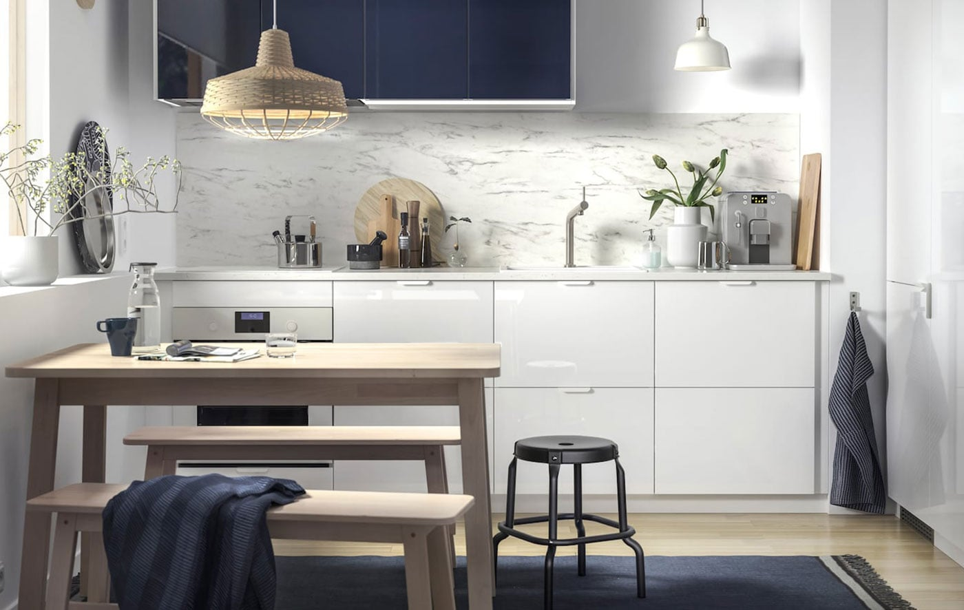 Merveilleux A Small, White Kitchen With Marble Effect Splashback And Dark Blue Wall  Cabinets.