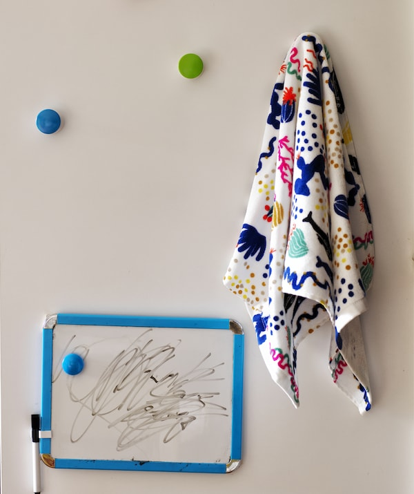 A small whiteboard and colourful LOSJÖN hooks holding a colourful towel.