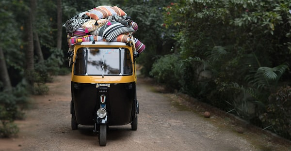 A small yellow and black coloured taxi in India carrying with colourful striped pillows on top.