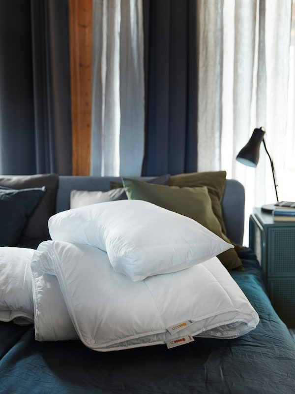 A SMÅSPORRE duvet and a SKOGSLÖK ergonomic pillow are piled-up together on a blue bed in a blue-toned bedroom.