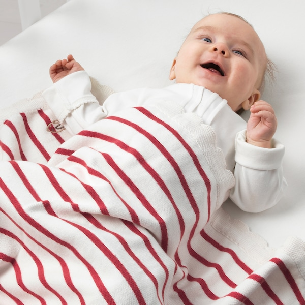 A smiling baby with a white and red striped RÖDHAKE blanket made from responsibly grown cotton.