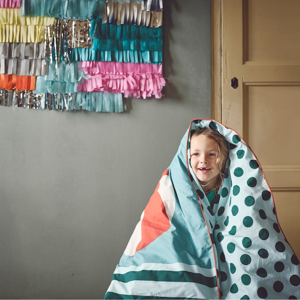 A smiling child is wrapped in a cosy KÄPPHÄST quilt cover with light and dark green polka dots and stripes.