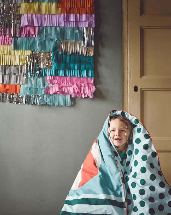 A smiling child is wrapped in a cozy KÄPPHÄST duvet cover with light and dark green polka dots and stripes.