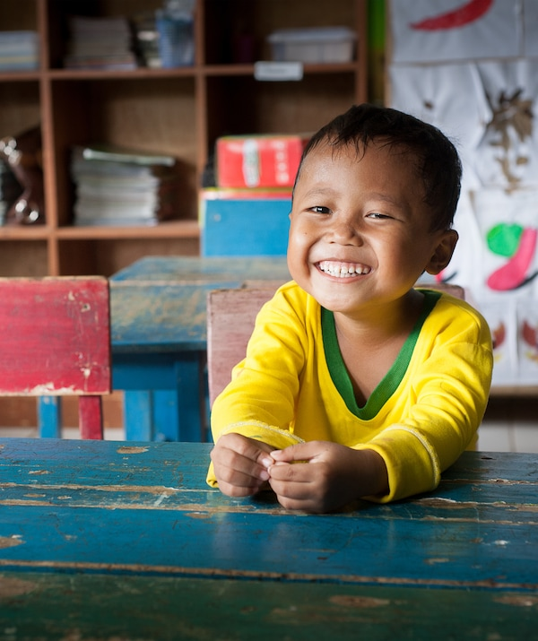 A smiling child sitting at a blue desk.