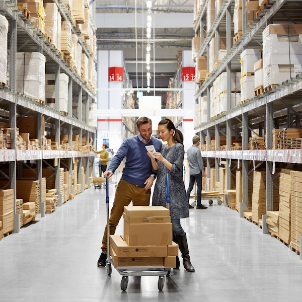 A smiling man with a trolley of IKEA furniture in a box and a talking woman with a ponytail is looking at a shopping list at the middle of IKEA self-serve warehouse.