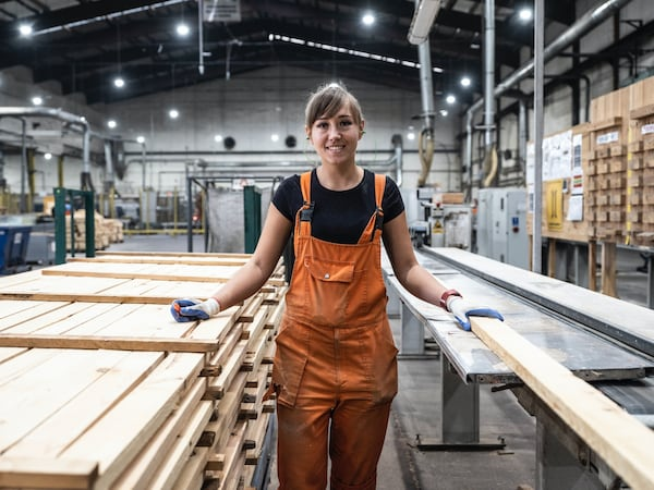 A smiling woman working at an IKEA supplier as she lifts up a stack of flattened white cardboard boxes.
