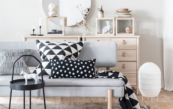A sofa in a light and bright living room with bold patterned black and white cushions.