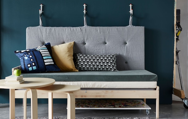 A sofa made from mattresses with the backrest hanging on wall hooks.