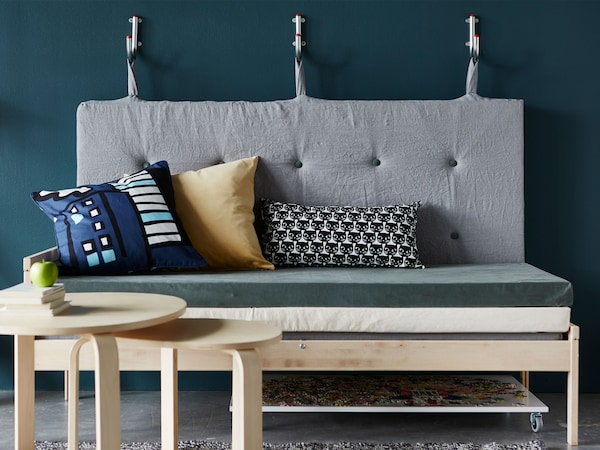 A sofa made from mattresses with the backrest hanging on wall hooks