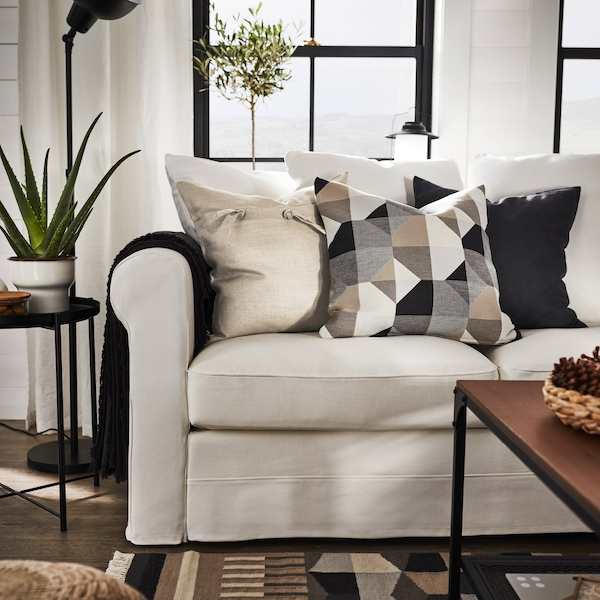 A sofa with a grey throw and decorative cushions in beige, black-grey and graphic patterns. A matching rug lies in front.