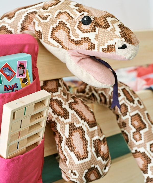 A soft toy python wrapped around the frame of a wooden bed, next to a fabric pocket storage accessory with books inside.