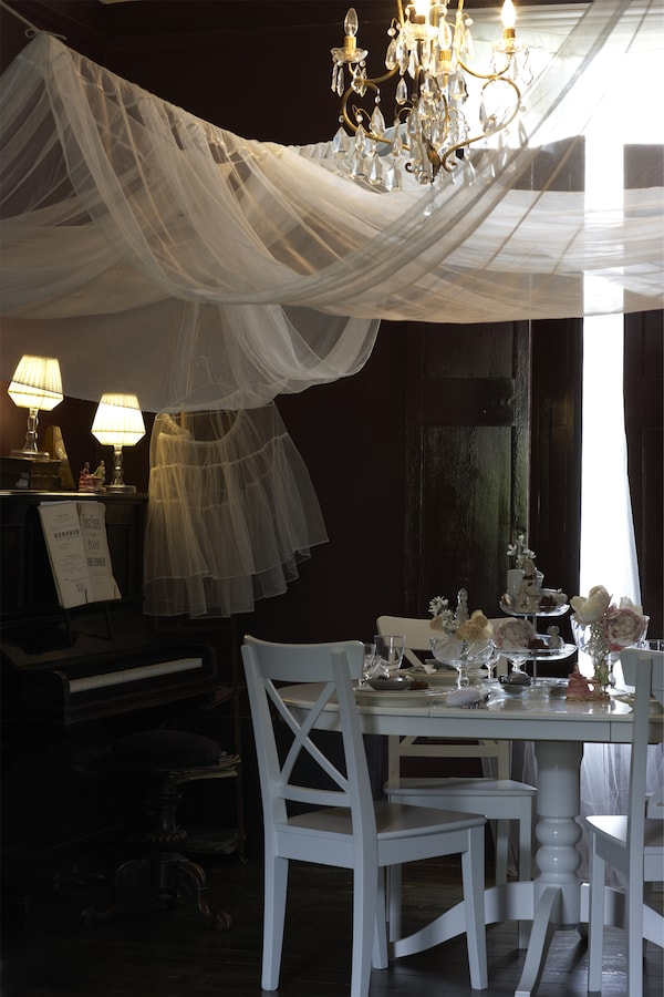 A softly lit theatrical chandelier and white dinner setting with table decorations.