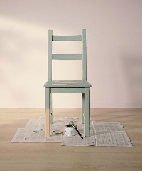 A solid wood chair half painted, sitting on an open newspaper with an open paint can and brush.